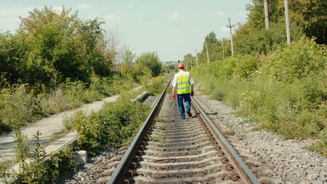 Rear view of senior engineer in uniform walks along track out of town in summer video