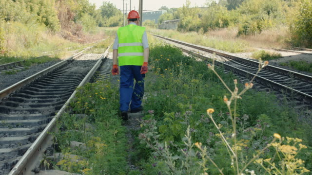 Rear view of senior engineer in uniform walks at tracks out of town in summer video