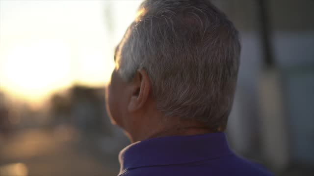 Rear view of senior man walking and looking away while thinking about life