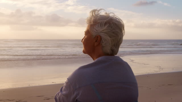 Rear View Of Senior Woman On Beach Watching Sun Set Over Ocean Rear view of thoughtful senior woman sitting on beach watching sun set over ocean waves - shot in slow motion independence stock videos & royalty-free footage
