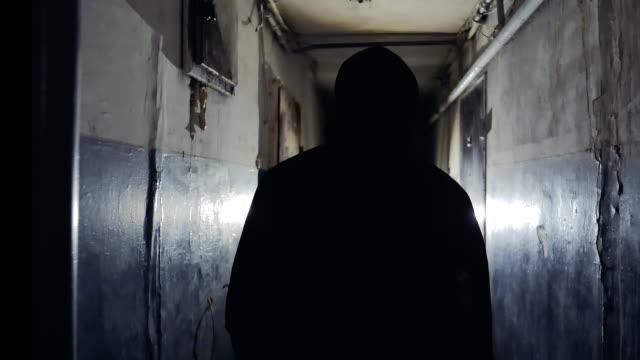 rear view of silhouette of a man in black jacket confidently walking away from camera - podświetlony filmów i materiałów b-roll