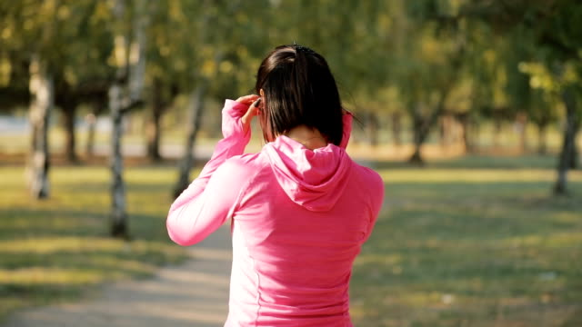 Rear view of sportswoman in pink sportswear jogging outdoors, healthy lifestyle concept. Slow motion. Rear view of sportswoman in pink sportswear jogging outdoors, healthy lifestyle concept. Slow motion. saturated color stock videos & royalty-free footage