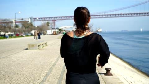 rear view of sporty girl running along embankment - capelli castani video stock e b–roll