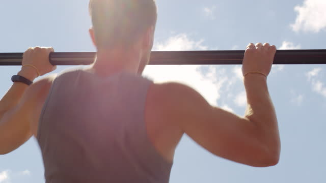 Rear View of Strong Man Doing Pull Ups on Bar Rear view of athletic man doing pull ups on bar while working out outdoors on bright summer day bodyweight training stock videos & royalty-free footage