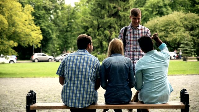 Rear view of students sitting on bench after exam Rear view of group of diverse students is sitting on the bench outside university after exam. Students are congratulating their happy friend with passing exam and give him a high five. behind stock videos & royalty-free footage