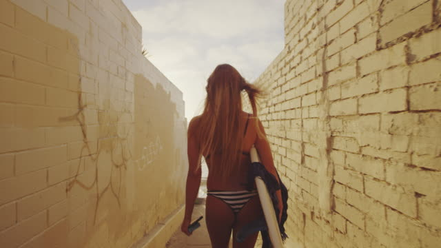 rear view of surfer girl walking with surfboard down alley to beach with surfboard under arm at sunset - opalenizna filmów i materiałów b-roll