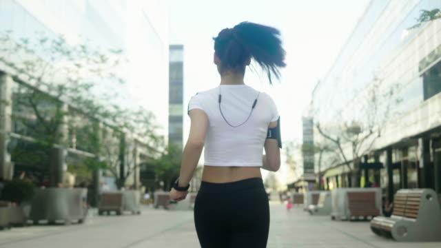 stockvideo's en b-roll-footage met achtermening van de agent in de stad - paardenstaart haar naar achteren