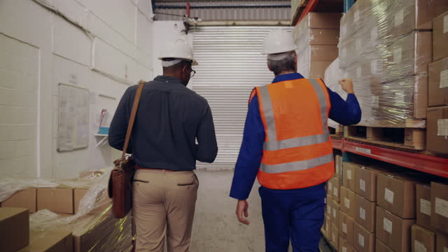Rear view of two multi ethnic worker and businessman walking near shelves of logistics factory
