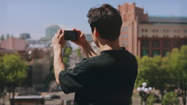 vidéos et rushes de vue arrière du touriste d'homme méconnaissable photographiant la ville par le smartphone - photophone