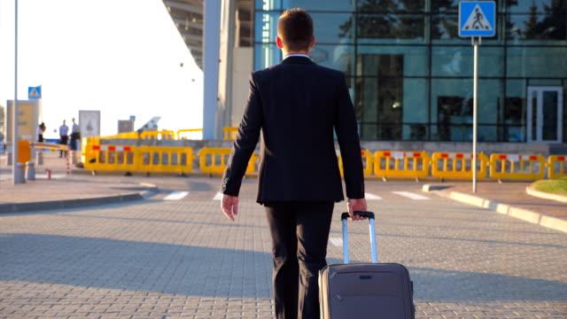 認識できない青年実業家の空港ターミナルに歩いて、日没時車輪でスーツケースを引いての後姿。彼の荷物と一緒に街に行く男性ビジネスの成功者。クローズ アップ - 後ろ姿点の映像素材/bロール