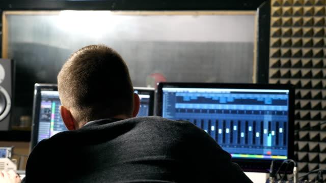 rückansicht des unkenntlich junge männliche ton-ingenieur und musikproduzent arbeiten im modernen tonstudio. audio-editor erstellen ein neues lied auf personal computer. slow-motion hautnah - aufnahmestudio stock-videos und b-roll-filmmaterial