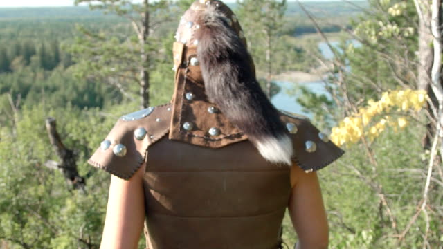 Rear view of warrior in old armor with fur that goes forest in summer video