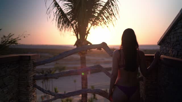 Rear view of woman admiring sunset from the hotel swimming pool area