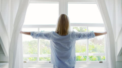 Rear View Of Woman Opening Curtains And Looking Out Of Window Rear view as woman wearing pajamas draws curtains and looks out of window - shot in slow motion morning stock videos & royalty-free footage