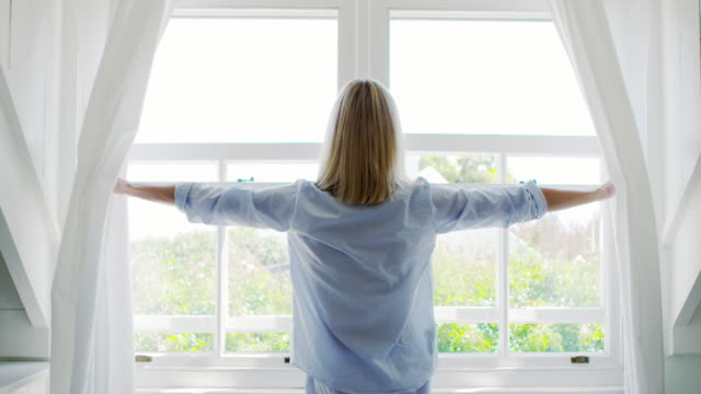 Rear View Of Woman Opening Curtains And Looking Out Of Window Rear view as woman wearing pajamas draws curtains and looks out of window - shot in slow motion chance stock videos & royalty-free footage
