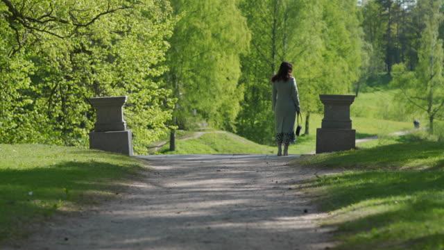 vídeos y material grabado en eventos de stock de vista trasera de la mujer de pie en sendero en el día soleado de primavera en el parque - espalda humana