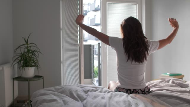 Video Rear view of woman stretching in bedroom