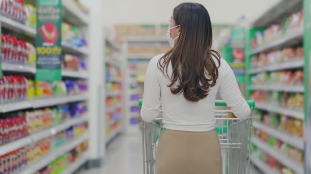 vídeos y material grabado en eventos de stock de vista trasera de mujer con carrito de la compra en el supermercado - snack aisle
