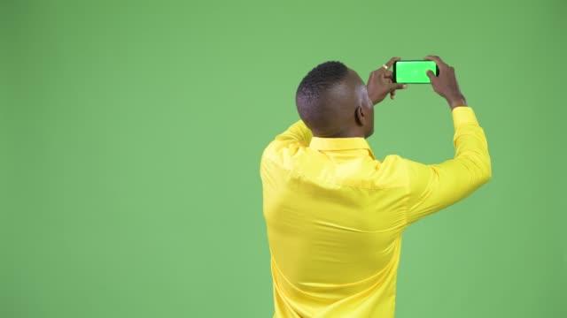 Opinião traseira o homem de negócios Africano novo que toma o retrato com telefone - vídeo