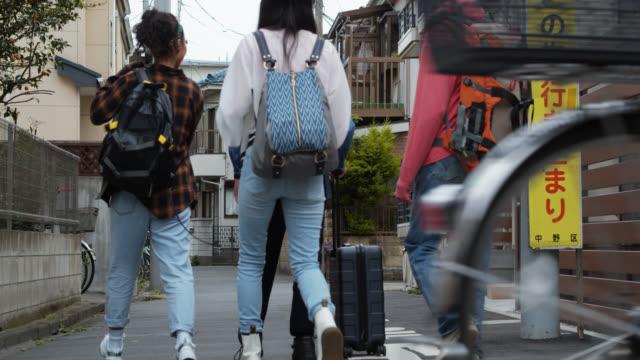 stockvideo's en b-roll-footage met rear view van jonge aziatische backpackers wandelen door residentiële wijk in japan - oost azië