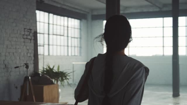 Vista trasera de la joven bailarina caminando en estudio - vídeo