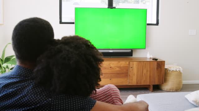 ホームと見てテレビ - スローモーションで撮影でソファーに座っていた若いカップルの背面図 - 居間点の映像素材/bロール
