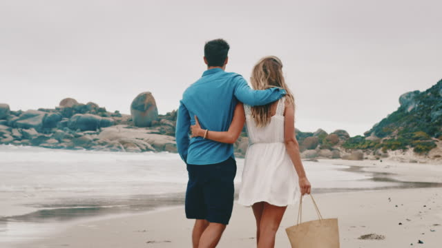 rear view of young couple walking at beach - attività del fine settimana video stock e b–roll
