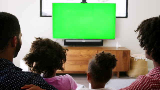 Rear view of young family sitting on sofa at home and watching television Rear view of young family sitting on sofa at home and watching television family watching tv stock videos & royalty-free footage