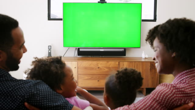Rear view of young family sitting on sofa at home and watching television