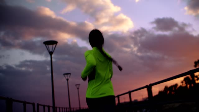 vídeos de stock e filmes b-roll de rear view of young fit woman running at sunset - young woman running city