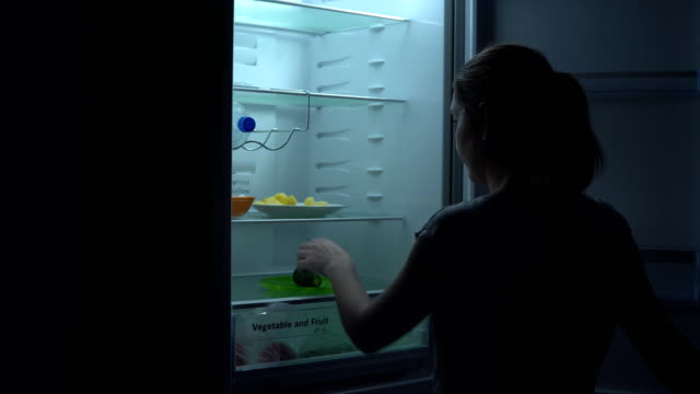 Rear view of young girl is hungry and takes cucumber from the refrigerator to have bite at night Rear view of young girl is hungry and takes cucumber from the refrigerator to have bite at night fridge stock videos & royalty-free footage