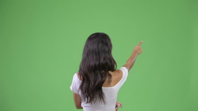 vídeos de stock e filmes b-roll de rear view of young multi-ethnic woman pointing finger - apontar sinal manual