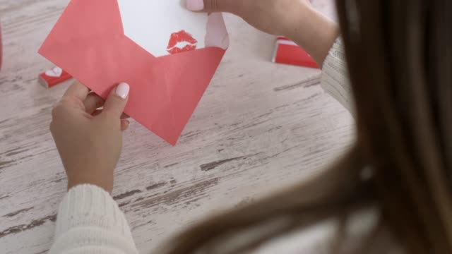 rear view of young woman opening her love letter - san valentino video stock e b–roll