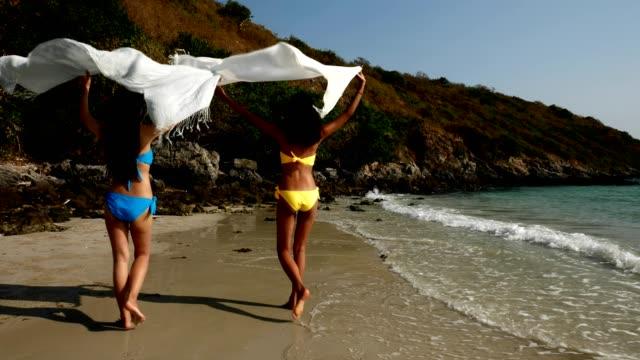 bakifrån av unga kvinnor i bikini med tyg promenader på stranden - sarong bildbanksvideor och videomaterial från bakom kulisserna