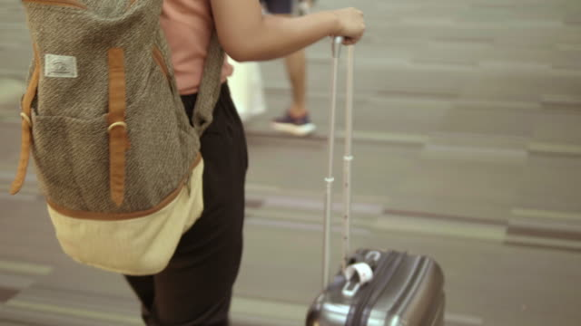 rear view  : people walking at the airport. - donna valigia solitudine video stock e b–roll