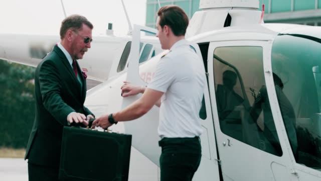 vídeos y material grabado en eventos de stock de vista trasera: empresario mayor caminando hacia el helicóptero - viaje en primera clase