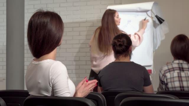 Foto de vista trasera de una empresaria escuchando a un orador en una conferencia de negocios - vídeo