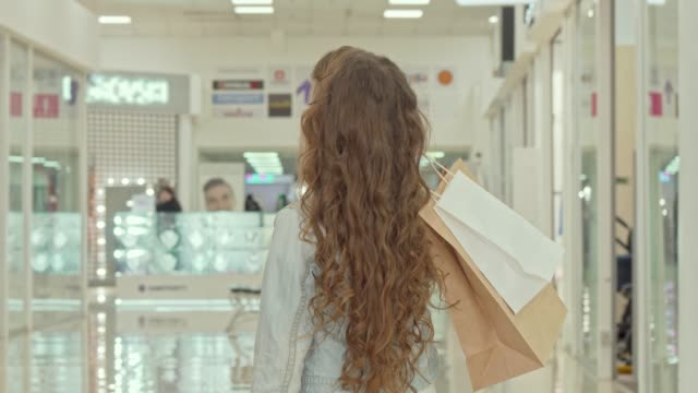 Rear view shot of a curly haired little girl looking at clothing stores at shopping mall
