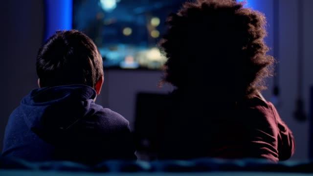 vídeos de stock, filmes e b-roll de meninos adolescentes da opinião traseira que lutam no jogo video em casa - game