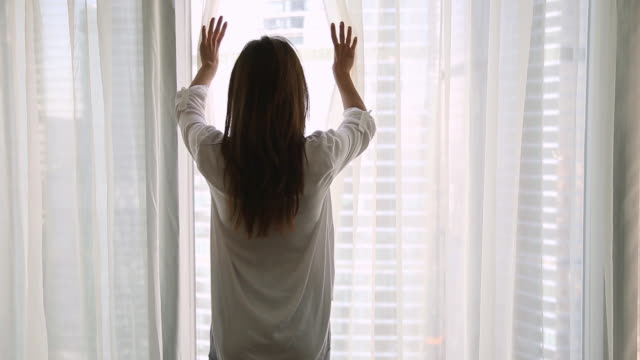 rear view woman starting day open curtains in the morning - настоящая жизнь стоковые видео и кадры b-roll