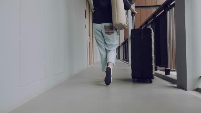 rear view : young woman carries suitcase - fare una prenotazione video stock e b–roll