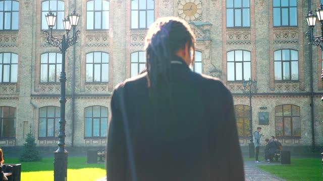 Rear-view of young African-American student with dreadlocks going to university in sunshine. Rear-view of young African-American student with dreadlocks going to university in sunshine locs hairstyle stock videos & royalty-free footage