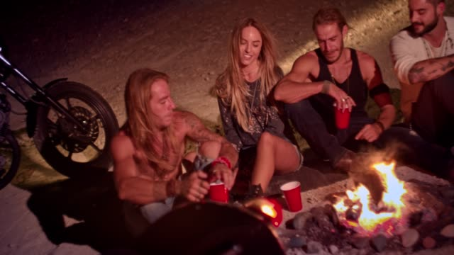 Rebel friends with motorcycles partying with alcohol around bonfire video
