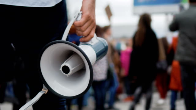 Rebel go on strike through crowd and holds in hand a megaphone or loudspeaker. 1 Man holds a megaphone in his hands, walking down street through many people on strike. Close up of one guy with loudspeaker in crowd at a demonstration 4k. Young adult boy on revolution. megaphone stock videos & royalty-free footage