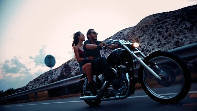 rebel motorcyclist with girlfriend riding motorbike on highway - motociclista video stock e b–roll