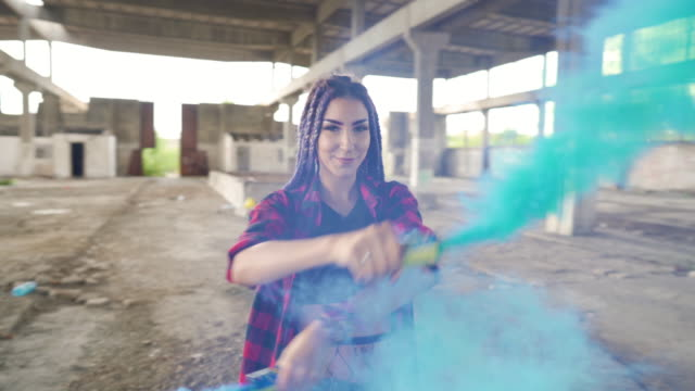 Rebel within Attractive young woman posing in an abandoned ruined industrial hall with a blue smoke bombs in her hands. urban fashion stock videos & royalty-free footage