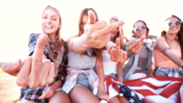 Rebellious teens showing their middle fingers and holding American flag video