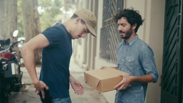 在房子前面接收包裹 - postal worker 個影片檔及 b 捲影像