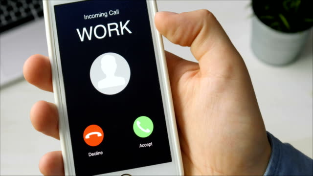 Receiving phone call from Work and accepting. Mobile communication concept. Sitting at the desk
