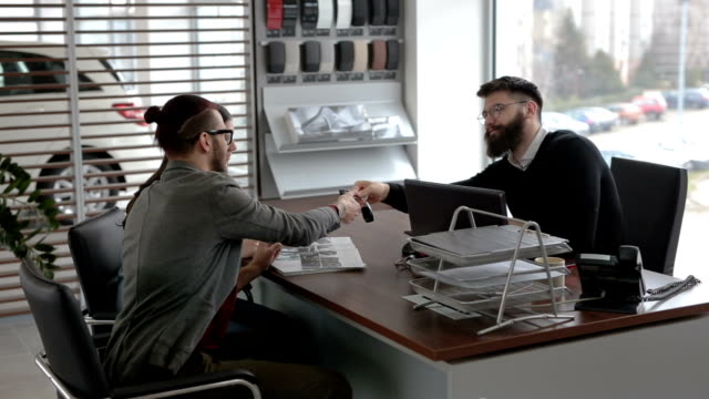 Receiving the car keys Young and handsome hipster man, buying a new car with his girlfriend, from the car saloon. car dealership stock videos & royalty-free footage